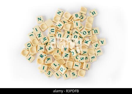 Pila di casuale gioco SCRABBLE lettera di piastrelle con valore di punteggio miscelati, visto dal di sopra, isolato su sfondo bianco. Foto Stock