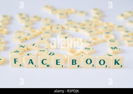"""Focus sulla parola """"Facebook"""" fatta di gioco SCRABBLE lettera di piastrelle con valore di punteggio, piastrelle casuale miscelato fino in background. Profondità di campo. Foto Stock"""