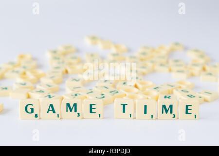 """Focus sulle parole """"tempo di gioco' fatto di gioco SCRABBLE lettera di piastrelle con valore di punteggio, piastrelle casuale miscelato fino in background. Profondità di campo. Foto Stock"""
