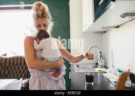 Azienda madre neonato in cucina mentre il tè Foto Stock