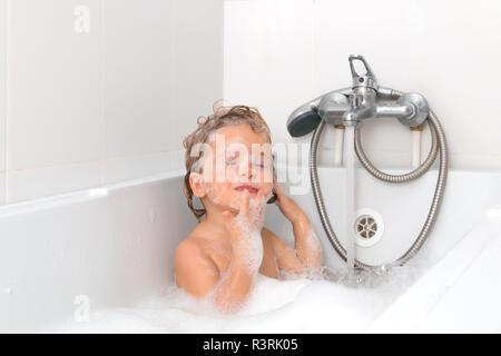Bimba bionda nel bagno con la schiuma sul suo viso. Gli occhi sono chiusi. Baby indipendenti di prendere un bagno su sfondo bianco. Lavaggio per neonati e balneazione. Igiene e Sanità. Foto Stock