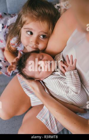 Madre tenendo il suo bambino vicino con la sorella sensazione i suoi capelli