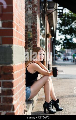 Giovane donna seduta in strada su una porta, tenendo una tazza di caffè Foto Stock