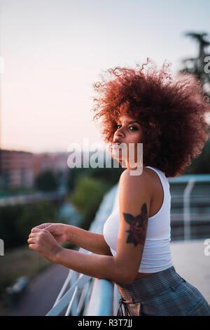 Ritratto di giovane donna in piedi sulla terrazza al crepuscolo serale