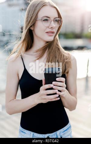 Giovane donna azienda tazza di caffè Foto Stock