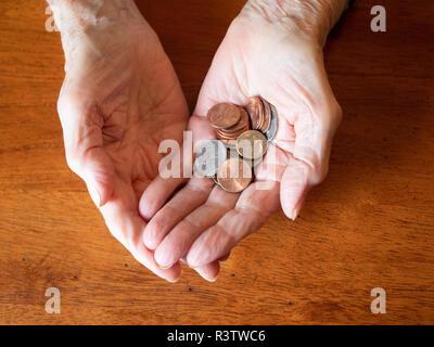 Ravvicinata di una donna anziana con le mani in mano azienda spiccioli, nickels e spiccioli. Fotografato da sopra con un tavolo di legno in background. Foto Stock