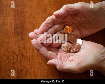Ravvicinata di una donna anziana con le mani in mano azienda spiccioli. Fotografato da sopra con un tavolo di legno in background e copia di spazio. Foto Stock