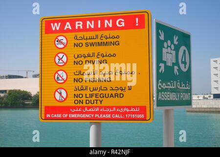 Bilingual cartelli di avvertimento, n. nuoto, immersione, pesca, niente bagnino di turno, il gruppo punto, in arabo e in inglese, Baia di Bahrain, Manama, Bahrain Foto Stock