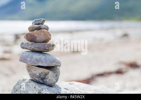 Equilibrio e armonia: pietre impilate sulla spiaggia Foto Stock