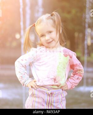 Ritratto di felice bambina vicino alla fontana nel parco della città Foto Stock