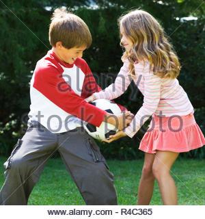 Ragazzo e ragazza che gioca con un calcio in un giardino Foto Stock