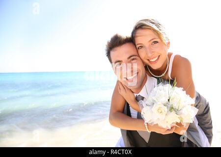 Lo sposo dando piggyback ride per la sua sposa Foto Stock