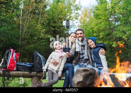 Famiglia con lo smartphone tenendo selfie vicino al fuoco