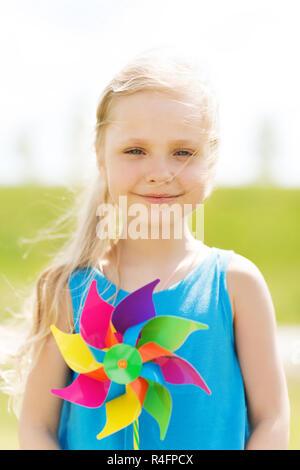 Felice bambina con la girandola colorata in estate Foto Stock