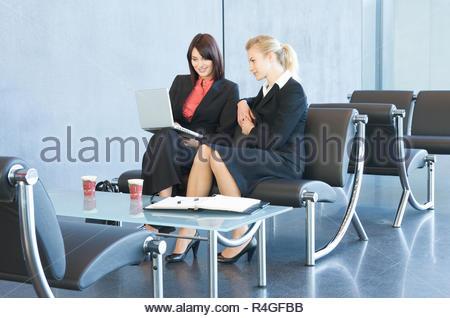 Due donne aventi un informale riunione aziendale, che guardano un notebook Foto Stock