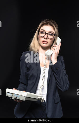 Bella giovane imprenditrice parla al telefono con filo isolato su nero Foto Stock