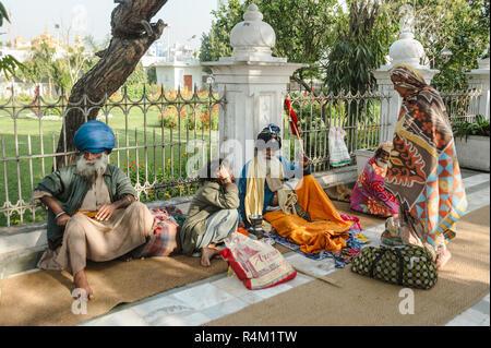Gruppo di indiani sikh si siede vicino tempio dorato. 26 febbraio 2018 Amritsar, India. Foto Stock