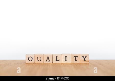 Focus sulla parola 'Qualità' fatta di blocco di legno dice con lettere su una tavola di legno. Profondità di campo. Copia dello spazio. Foto Stock