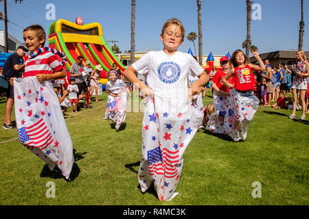 Utilizzando sacchi decorata con la bandiera statunitense, bambini competere in un quarto di luglio festival gara di sacco in Newport Beach, CA. Foto Stock