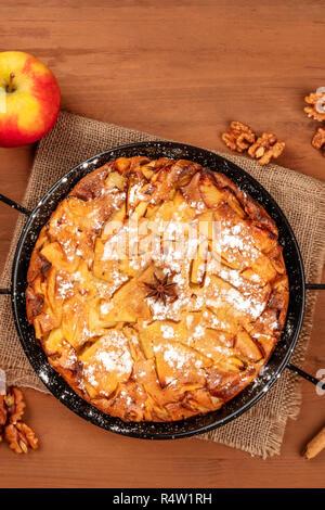 Un primo piano di una fetta di torta di mele, girato dalla parte superiore al buio su un rustico sfondo di legno con un apple, noci, anice, e di un posto per il testo Foto Stock