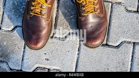 Prospettiva in prima persona di scarpe. Passeggiata invernale concetto. Vista da sopra su marrone stivali su cobblestone pavement sfondo Foto Stock