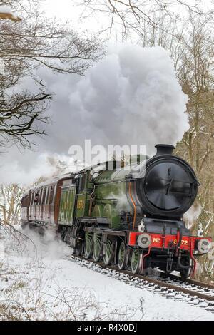 Ritratto di avvicinarsi al Regno Unito locomotiva a vapore puffing nella neve sul Severn Valley Railway linea Heritage, lasciando fuori vapore. Nevoso, scena d'inverno. Foto Stock
