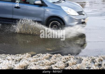 Schizzi da sotto le ruote della vettura. Sullo sfondo delle intemperie fondere la neve sulle strade. Sfocatura del movimento Foto Stock