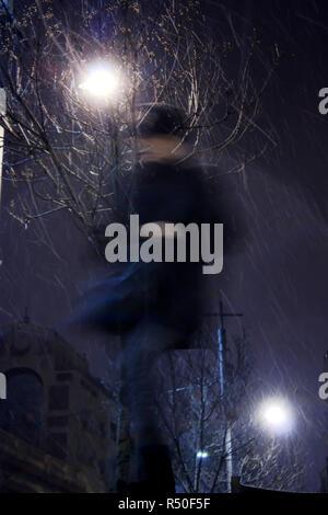 Sfocata persona camminare da solo in presenza di neve e di vento per le strade delle città nella notte invernale , basso angolo di visione Foto Stock