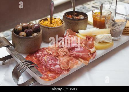 Portoghese - tapas di prosciutto affumicato salame chorizo salsicce, una varietà di formaggio, cracker, il patè di fegato e diverse marmellate tradizionali Foto Stock