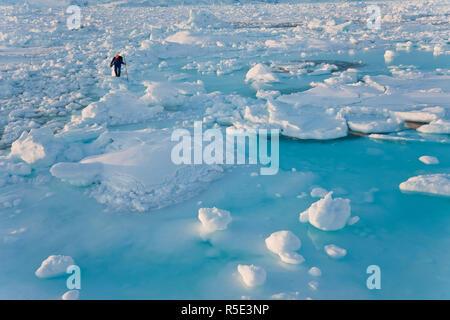 Il cacciatore di tenuta sul mare di ghiaccio, Tiniteqilaq, E. Groenlandia Foto Stock