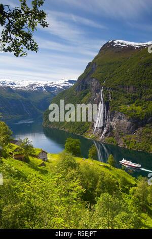 Una nave traghetto passa al disotto di una vecchia fattoria abbandonata e le Sette Sorelle cascata, Geiranger Fjord, Geiranger, More og Romsdal, Norvegia