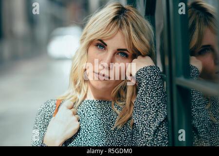 Ritratto di grave giovane donna bionda in piedi sul background urbano. Bellissima ragazza con gli occhi blu di indossare abiti in piedi all'esterno.