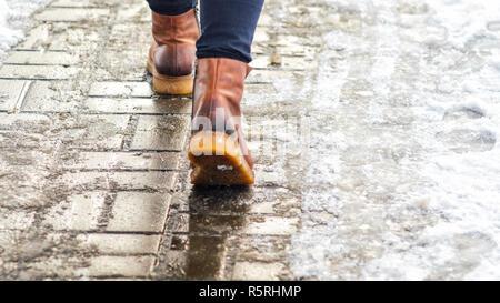 A piedi su bagnato ghiaccio fuso marciapiede. Vista posteriore sui piedi di un uomo che cammina lungo la ghiacciate. Coppia di scarpa sulla strada ghiacciata in inverno. Abstract vuoto bla Foto Stock