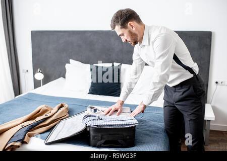 Imprenditore elegante imballaggio i suoi vestiti in valigia sul letto della camera in hotel durante il viaggio di affari Foto Stock