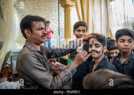 Un ragazzo che viene dipinto baffi prima di una performance, Pushkar, Rajasthan, India