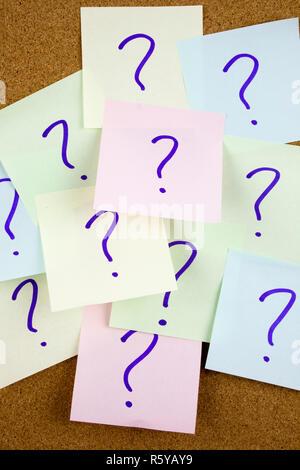 Un bigliettino giallo iscritto, didascalia, iscrizione pila di carta colorata note con un punto interrogativo. Primo piano. Foto Stock