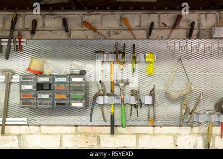 Vecchi strumenti appeso alla parete in lamiera officina , ripiano porta attrezzi contro una parete