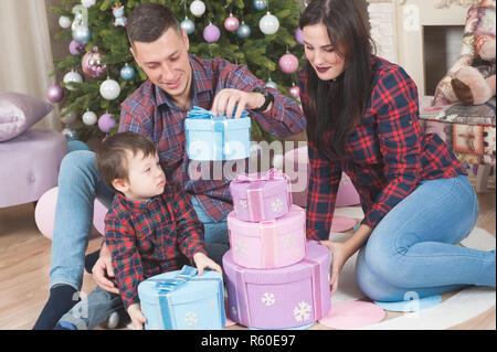 Felice famiglia giovane madre padre e bambino tenendo il natale confezioni regalo seduti a casa nelle decorazioni di Natale Foto Stock