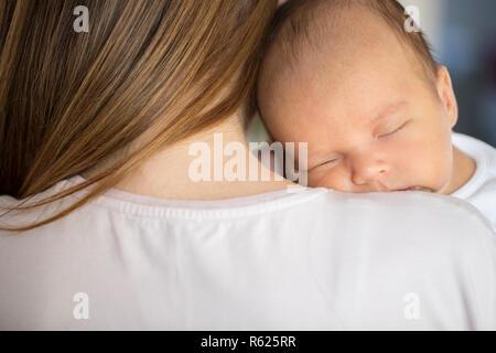 Amorevole Madre Cuddling Sleeping neonato Figlio sulla spalla Foto Stock