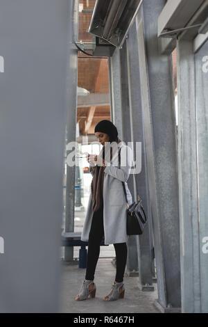 Donna che utilizza il telefono cellulare in piattaforma