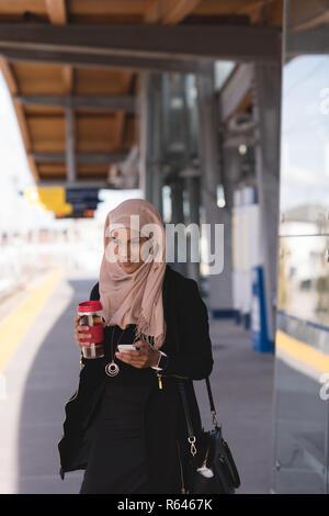 Donna che utilizza il cellulare mentre un caffè nella piattaforma alla stazione ferroviaria
