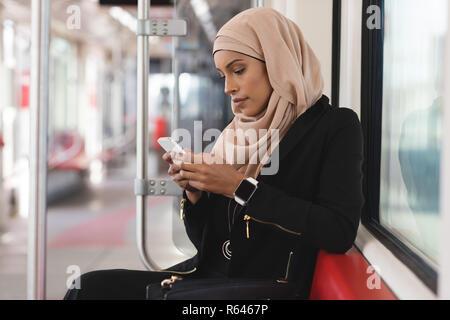 Donna che utilizza il telefono cellulare mentre si è in viaggio in treno
