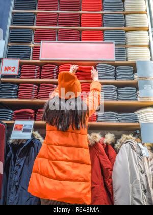 La ragazza tiene fuori la sua mano per i vestiti su scaffale del negozio. shopper tira su una cosa in un negozio di abbigliamento. Vista posteriore della donna che tiene una mano ad un ripiano con vestiti visualizzato nel negozio. Foto Stock