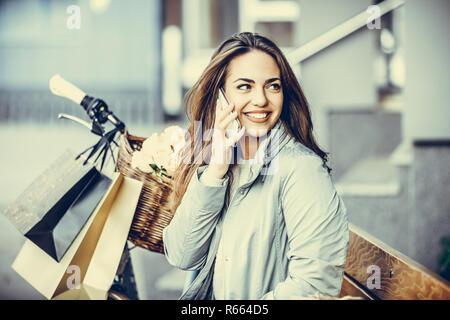 Felice giovane donna parlando al telefono cellulare durante la seduta sul banco in città Foto Stock