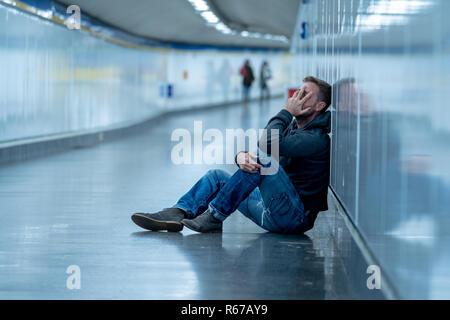 Giovane triste piangere la sofferenza della depressione stress seduta sul terreno street subway tunnel alla ricerca disperata appoggiata sulla parete da soli in disordine mentale Emo