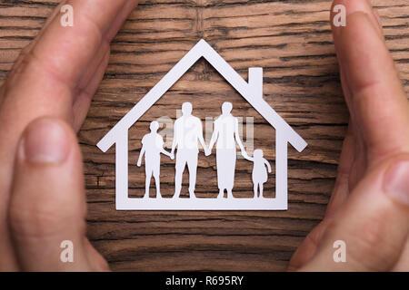 Persona in possesso di mano protettrice su casa famiglia Foto Stock
