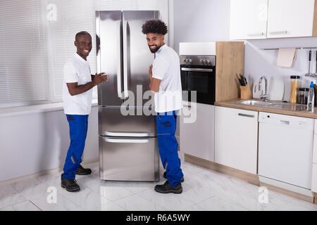 Due maschio Movers che fissa il congelatore in cucina Foto Stock