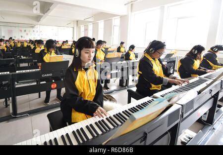 Shijiazhuang cinese nella provincia di Hebei. 5 Dic, 2018. Gli studenti imparano a suonare la tastiera elettronica a Dingzhou istruzione professionale centro in Shijiazhuang, a nord della Cina di nella provincia di Hebei, Dicembre 5, 2018. Il centro si è espresso a favore di una combinazione di istruzione professionale e di formazione in servizio e ottimizzato un orientati alla domanda del sistema educativo. Credito: Zhu Xudong/Xinhua/Alamy Live News Foto Stock