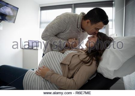 Affettuosa marito baciare la fronte della moglie incinta in clinica sala esame Foto Stock