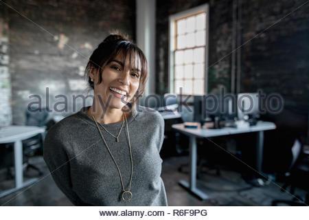 Ritratto sorridente, entusiasta imprenditrice creativa in office Foto Stock